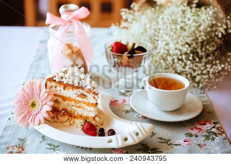 Tasty oldfashioned cake with cream icing served with tea and raw apples on shabby turquoise table. poster