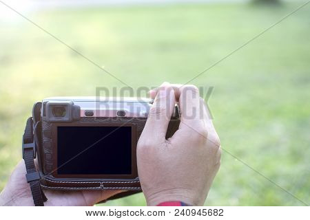 The Digital Dslr Camera In A Woman Hand. Blank Screen Of Camera On Female Hand To Take A Photo In Th