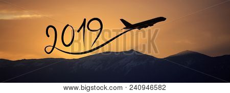 New year 2019 drawing by flying airplane on the air at sunrise, banner