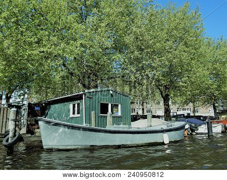 A Green Boat Parked At A Canal. Taken In Amsterdam.