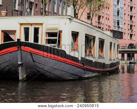 White Ship With A Black Strip And A Red Strip. Parked On A Canal. Taken In Amsterdam.