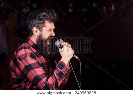 Man With Tense Face Holds Microphone, Singing Song, Black Background, Copy Space. Musician With Bear