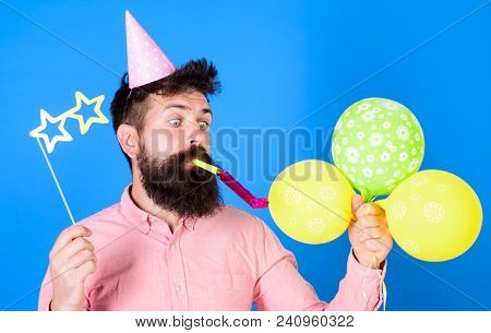 Hipster With Star Shaped Glasses Blows Into Party Horn. Surprise Concept. Guy In Party Hat With Holi