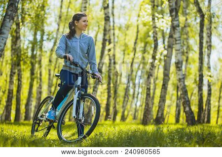 Cute Woman Cyclist Cycling Mountain Bike On The Birch Forest Trail