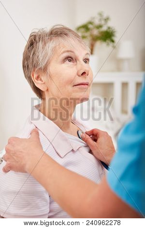 Nurse examine senior woman with dementia using stethoscope