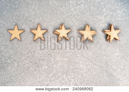 Five Wooden Stars In Piles Of 1, 2, 3, 4 And 5 Pieces On A Silver Background, Top View With Copy Spa