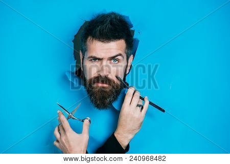 Serious Bearded Man Peeping Through Blue Paper Hole, Holds Scissors And Straight Razor In Hands. Man