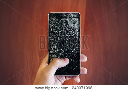 Cracked Smartphone In Hand Holding. Guy Holds The Phone With A Broken Display Glass In Hand On Backg
