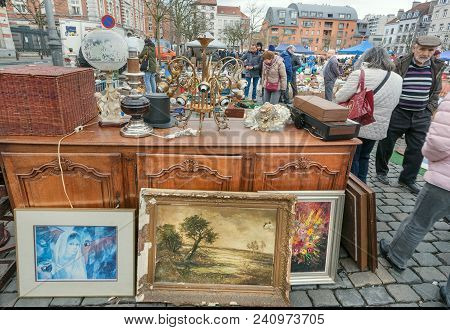 Brussels, Belgium - Apr 3: Buyers Of Popular Art And Flea Market With Bargains, Antique Stuff In Mes