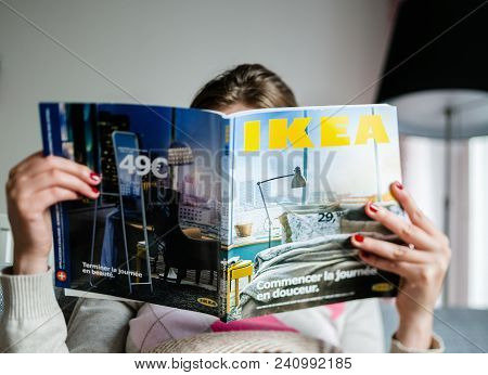 Paris, France - Aug 24, 2014: Woman Reading Ikea Magazine In Living Room