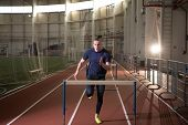 The shot of concentrated male track and field athlete hurdling.Indoor training poster