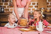 cropped shot of mother putting pancakes on table and looking at cute smiling kids having breakfast, 50s style family poster