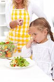 Mother training a healthy eating habit in her child - eating vegetable salad poster