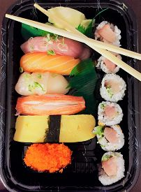 Takeout Sushi. Assorted Nigiri Sushi And A Yellowtail And Scallion Sushi Roll With Chopsticks In A T