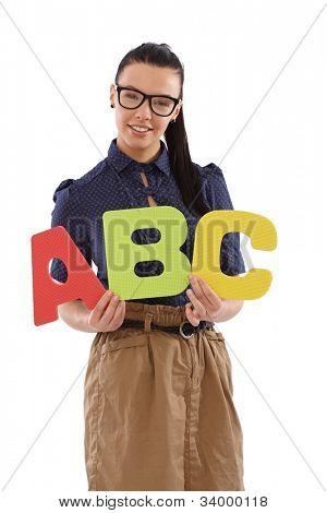 Pretty schoolmistress holding capital letters abc in hands, smiling.