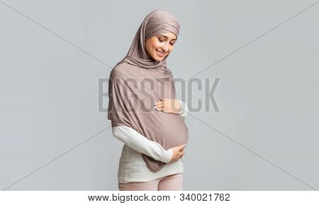 Enjoying Pregnancy. Pregnant Muslim Woman In Headscarf Tenderly Touching Her Belly, Embracing Tummy