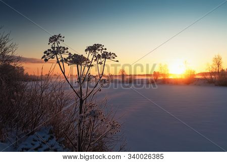 The Sun Sets Over A Frozen River In The Northern Finland. The Mist Rises From The River And Covers T