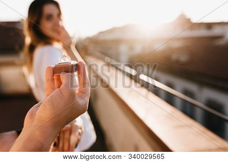 Man Makes Offer Of Marriage To Girl Standing On The Roof On A Sunny Day. Outdoor Portrait Of Young W