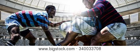 Rugby players against rugby goal post on a sunny day in the stadium