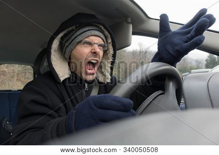 Angry Caucasian Man With Gloves Screaming With Gesture Into Car In Winter Time. Stressed Man Into Ve