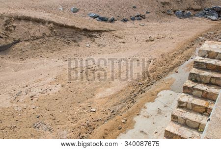 Sand, Stones And Ladder On The Building Or Pit In Spain. Nature Texture And Grit In Summer Sun Day.