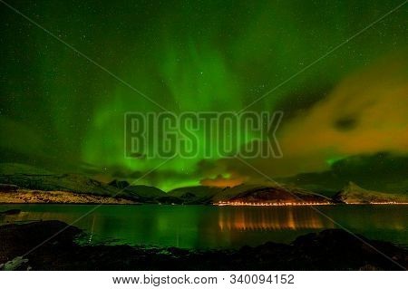 Polar Lights Aurora Borealis, Northern Lights With Many Clouds And Stars In The Sky Over Mountains I