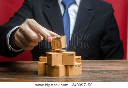 A Businessman Is Building A Stack Of Cardboard Boxes. Business Management, Problem Solving Support.