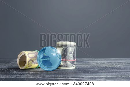 Money Bundle Rolls World Currencies And A Blue Glass Globe. Capital Investment, Savings. Profit Inco