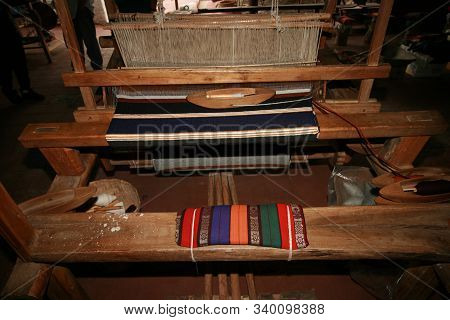 Traditional Wooden Loom With Blanket Being Woven And Blanket Folded And Used For Cushion On Loom Ben