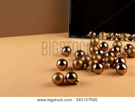 Reflection Of Group Of Christmas Balls And Shadow From Balls In A Mirror On Beige Surface.