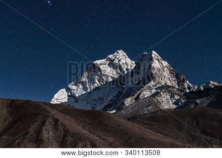 Ama Dablam Mountain Peak Lit Up By A Bright Moonlight On A Starry Night. Beautiful Night Mountain La