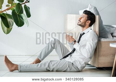 Side View Of Handsome Bi-racial Businessman Holding Cup Of Coffee In Morning