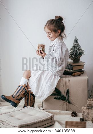 Stock Photo -  Beautiful Little Girl With Jars In Which Honey And Nuts With Wooden Christmas Decor