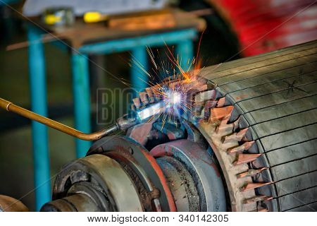 African man with a torch heating a rotor of an opened case motor , rewinding a giant electric motor