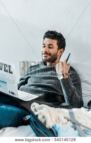 Handsome And Smiling Bi-racial Man In Sweater Reading Newspaper