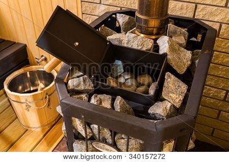Relax In A Hot Sauna. Hot Stone On Heater In Sauna Spa  Room. Sauna Baked Stove And Wooden Backgroun