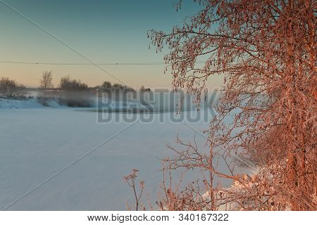 The Winter Sun Rises Over The Icy River At The Northern Finland. The Mist Rises From The Cold River