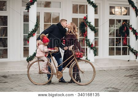 Affectionate couple kissing with daughter on bike. poster