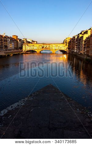 Vertical Crop Ponte Vecchio Bridge With Reflection At Sunset In Florence