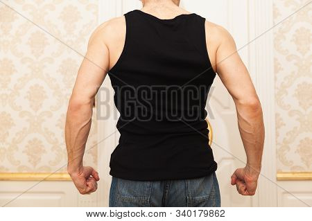 Young aggressive Caucasian man in black shirt clenches his fists menacingly near white door, back view, domestic violence concept poster