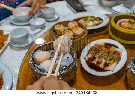 People Using Chopsticks And Having Hong Kong Dimsum In Restaurant