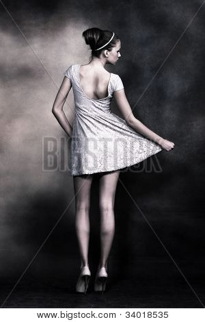 young gentle woman with bun styled hair in delicate lacy dress, full body shot, back view,