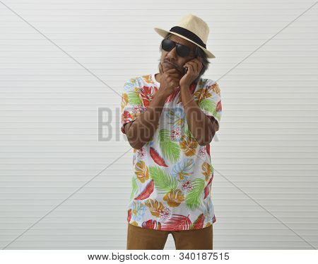 Thoughtful Elderly Traveler Asian Man Wearing Summer Shirt, Straw Hat And Sunglasses Talking With Sm