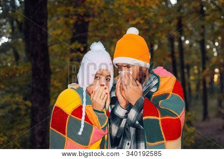 Showing Sick Couple Sneezing At Autumn Park. Girl With Handkerchief And Sneezing Boy In Autumn Park.