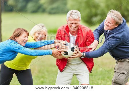 Active seniors struggle with each other for a football in the park and have fun