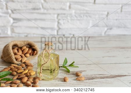 Almond Oil In Bottle And Almond Nuts On Wooden Background.