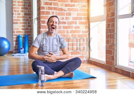Middle age handsome sportman sitting on mat doing stretching yoga exercise at gym smiling and laughing hard out loud because funny crazy joke with hands on body.
