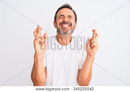Middle age handsome man wearing casual t-shirt standing over isolated white background gesturing finger crossed smiling with hope and eyes closed. Luck and superstitious concept.