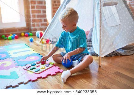 Young caucasian kid playing placing numbers at kindergarten. Preschooler boy doing maths at playroom.