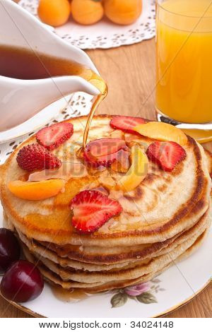 stack of pancakes slathered with syrup pored on and orange juice poster
